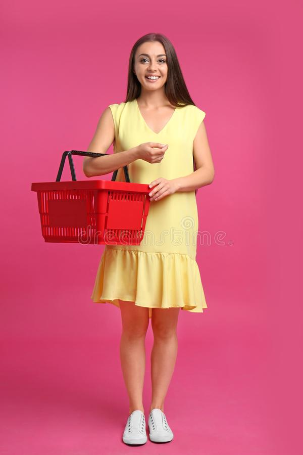 Giovane donna con acquisto vuoto sul fondo rosa immagini stock