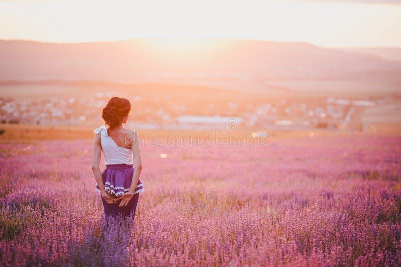 Giovane donna con bei capelli che stanno in un giacimento della lavanda al tramonto fotografie stock
