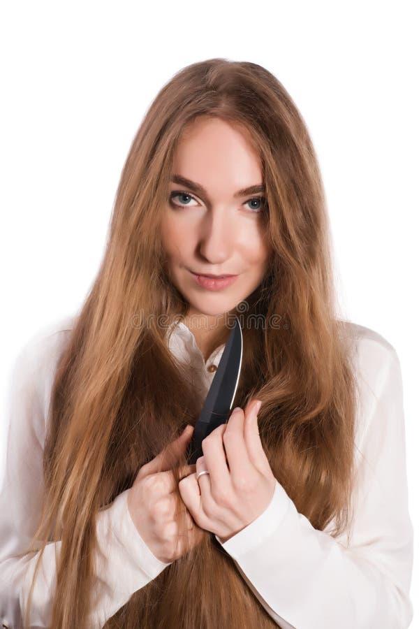Giovane donna con bei capelli e un coltello in sue mani fotografia stock
