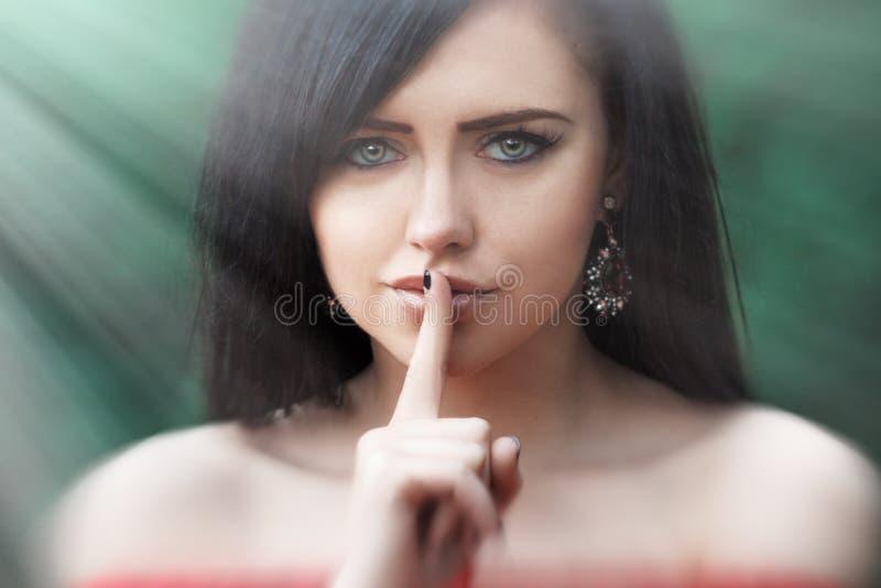 Giovane donna con capelli lunghi scuri che dice zitto con l'indice sulle labbra Gesto di silenzio fotografie stock