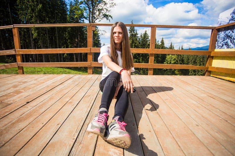 Giovane donna con capelli lunghi sul recinto del terrazzo godere di bella vista delle montagne fotografia stock