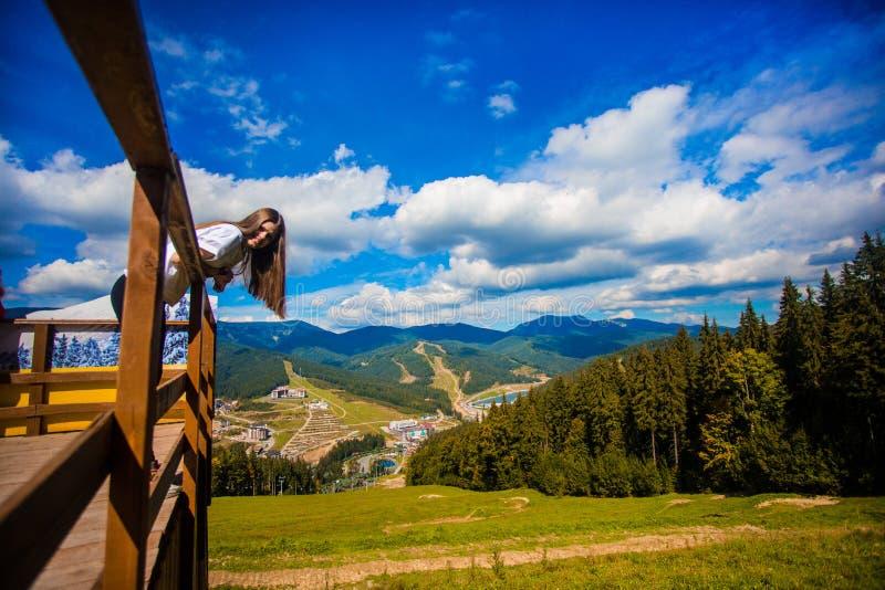 Giovane donna con capelli lunghi sul recinto del terrazzo godere di bella vista delle montagne immagini stock