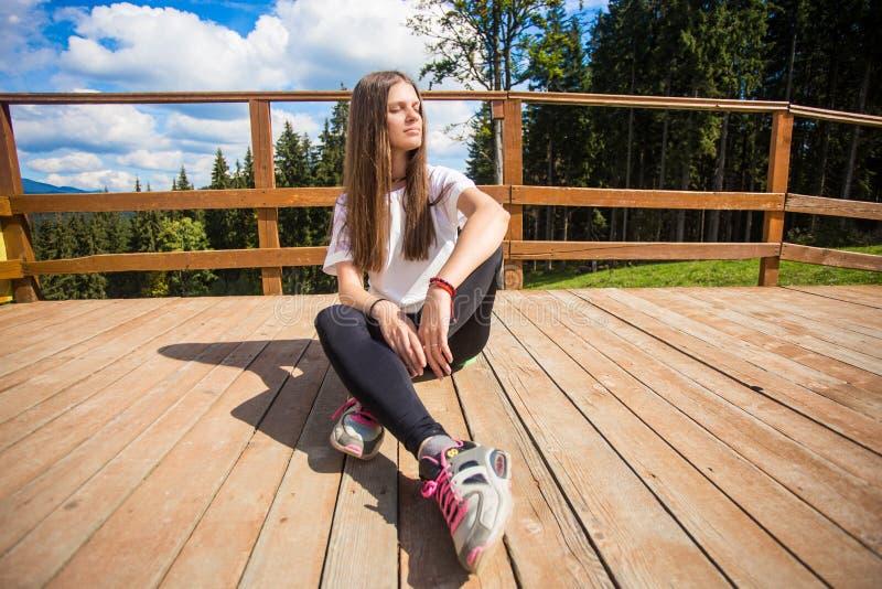 Giovane donna con capelli lunghi sul recinto del terrazzo godere di bella vista delle montagne fotografia stock libera da diritti