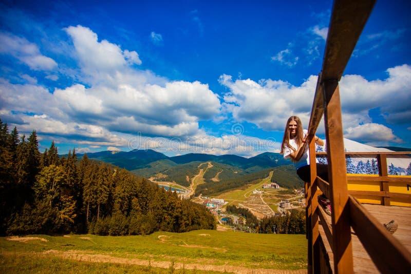 Giovane donna con capelli lunghi sul recinto del terrazzo godere di bella vista delle montagne immagine stock
