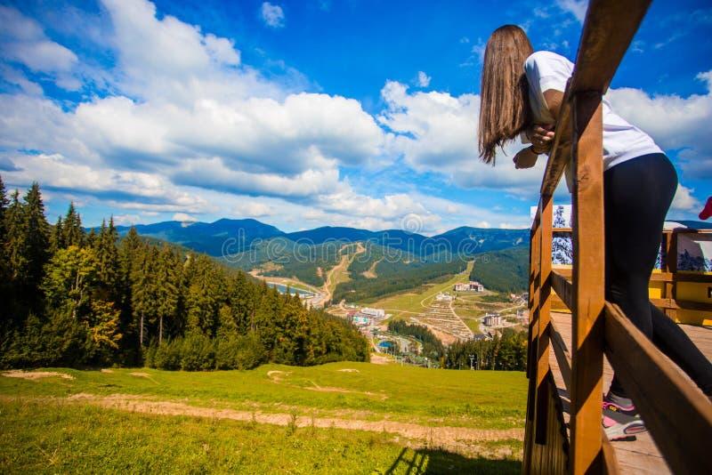 Giovane donna con capelli lunghi sul recinto del terrazzo godere di bella vista delle montagne immagine stock libera da diritti