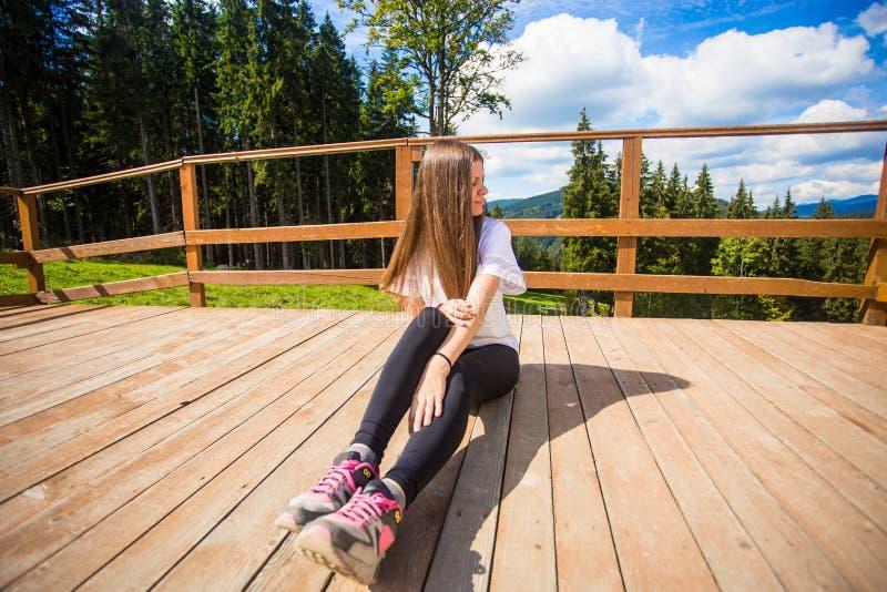 Giovane donna con capelli lunghi sul recinto del terrazzo godere di bella vista delle montagne fotografie stock