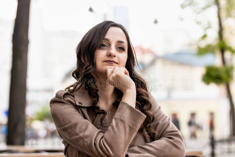 Giovane donna con capelli marroni lunghi ad una tavola contro lo sfondo della via, esaminante vago la distanza fotografia stock libera da diritti