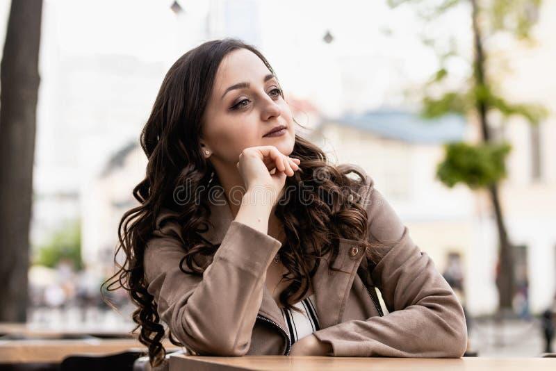 Giovane donna con capelli marroni lunghi ad una tavola contro lo sfondo della via fotografia stock libera da diritti