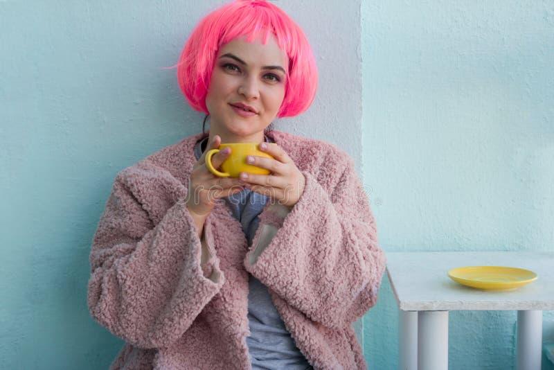 giovane donna con capelli rosa in pelliccia rosa che si siede nella caffetteria e che tiene tazza da caffè gialla fotografia stock