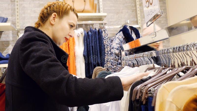 Giovane donna con capelli rossi che guardano tramite i nuovi vestiti durante l'acquisto fotografie stock