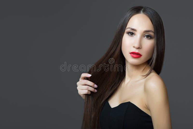 Giovane donna con capelli scuri diritti lunghi Pelle perfetta del rossetto rosso Fondo scuro fotografie stock libere da diritti