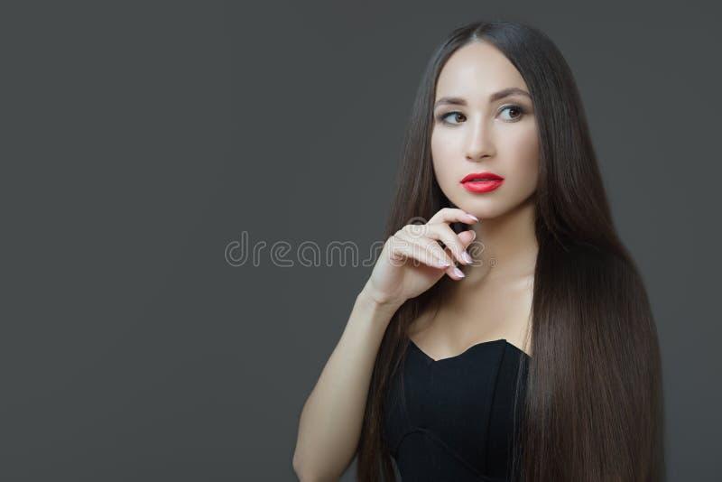 Giovane donna con capelli scuri diritti lunghi Pelle perfetta del rossetto rosso Fondo scuro immagini stock libere da diritti
