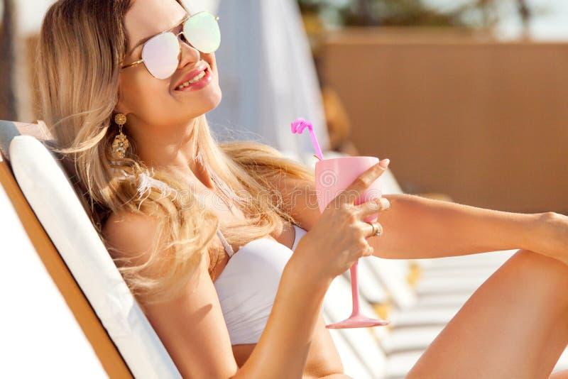 Giovane donna con coctail sulla spiaggia ad estate fotografia stock libera da diritti