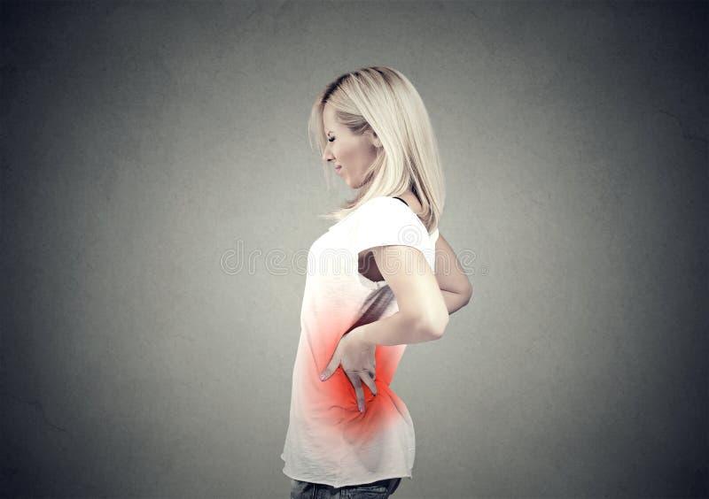 Giovane donna con dolore lombo-sacrale colorata nel rosso fotografia stock libera da diritti