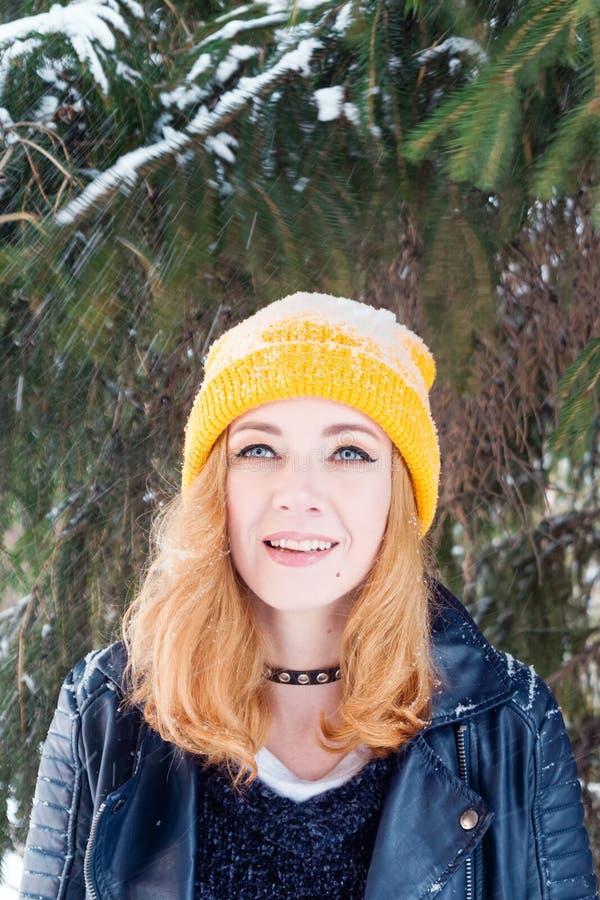 Giovane donna con gli occhi azzurri ed i capelli biondi in un cappello tricottante giallo sotto l'albero di abete al momento di fotografia stock libera da diritti