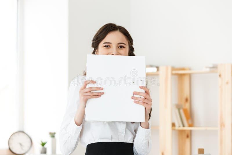 Giovane donna con gli occhi sorpresi o felici che danno una occhiata fuori da dietro il manifesto di carta Donna di affari che ti fotografia stock
