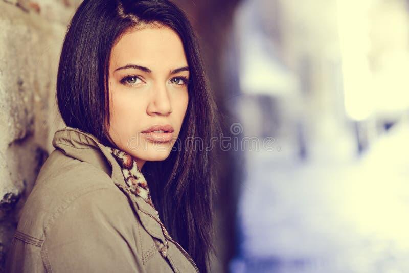 Giovane donna con gli occhi verdi nel fondo urbano fotografia stock libera da diritti