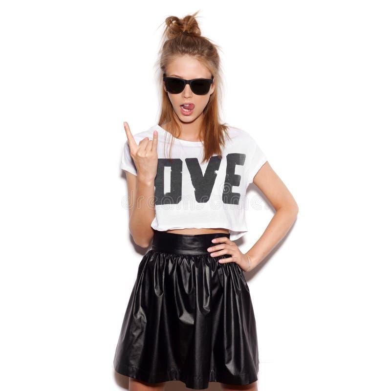 Giovane donna con gli occhiali da sole che danno il segno di rock-and-roll fotografia stock
