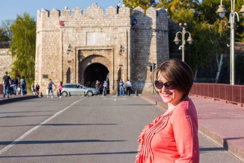 Giovane donna con gli occhiali da sole che stanno sul ponte in mezzo alla via ed a sorridere immagini stock