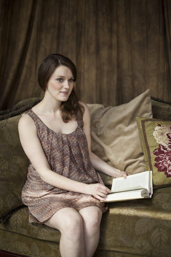 Giovane donna con i bei occhi verdi che legge un libro. fotografie stock