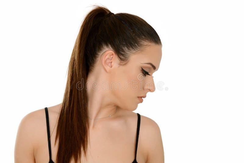 Giovane donna con i capelli marroni brillanti sani messi in coda di cavallino fotografia stock