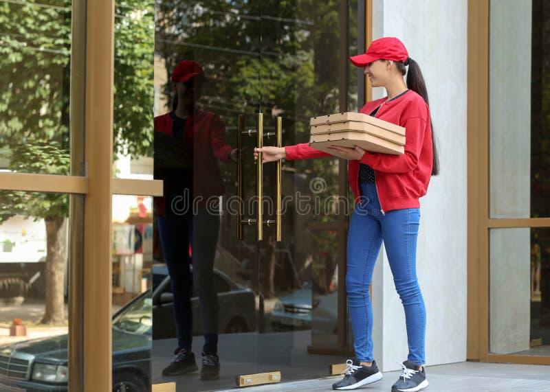 Giovane donna con i contenitori di pizza all'aperto Servizio di distribuzione dell'alimento fotografia stock libera da diritti