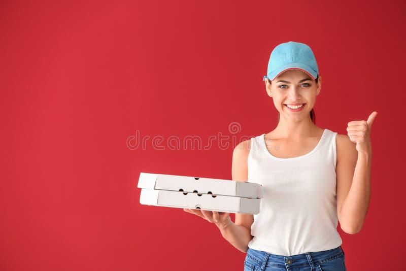 Giovane donna con i contenitori di pizza che mostrano gesto del pollice-su sul fondo di colore Servizio di distribuzione dell'ali fotografia stock
