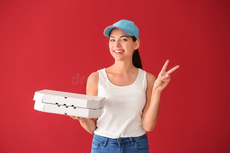 Giovane donna con i contenitori di pizza che mostrano il segno di vittoria sul fondo di colore Servizio di distribuzione dell'ali fotografie stock libere da diritti