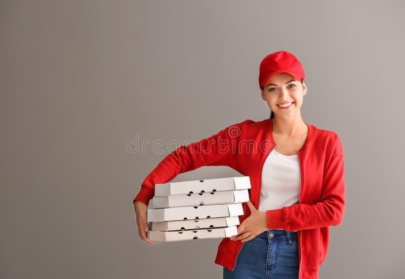 Giovane donna con i contenitori di pizza su fondo grigio Servizio di distribuzione dell'alimento fotografie stock