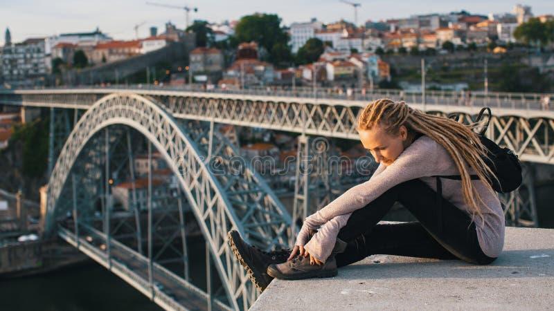 Giovane donna con i dreadlocks biondi che si siedono sui precedenti del ponte di Dom Luis I, Oporto fotografia stock libera da diritti