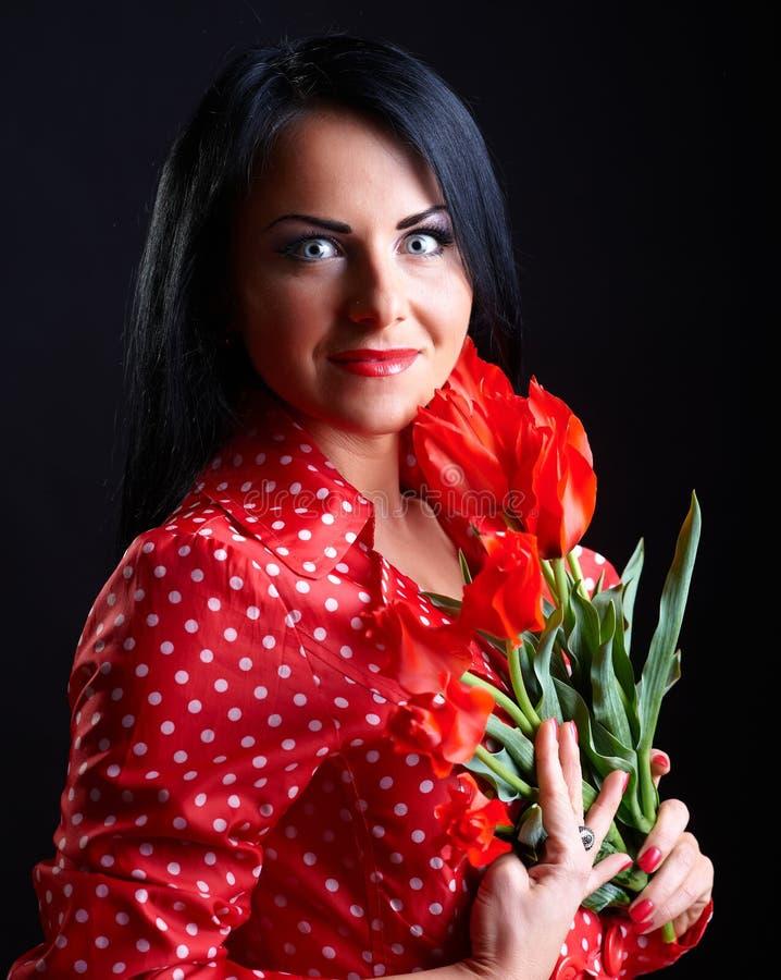 Giovane donna con i fiori rossi immagini stock
