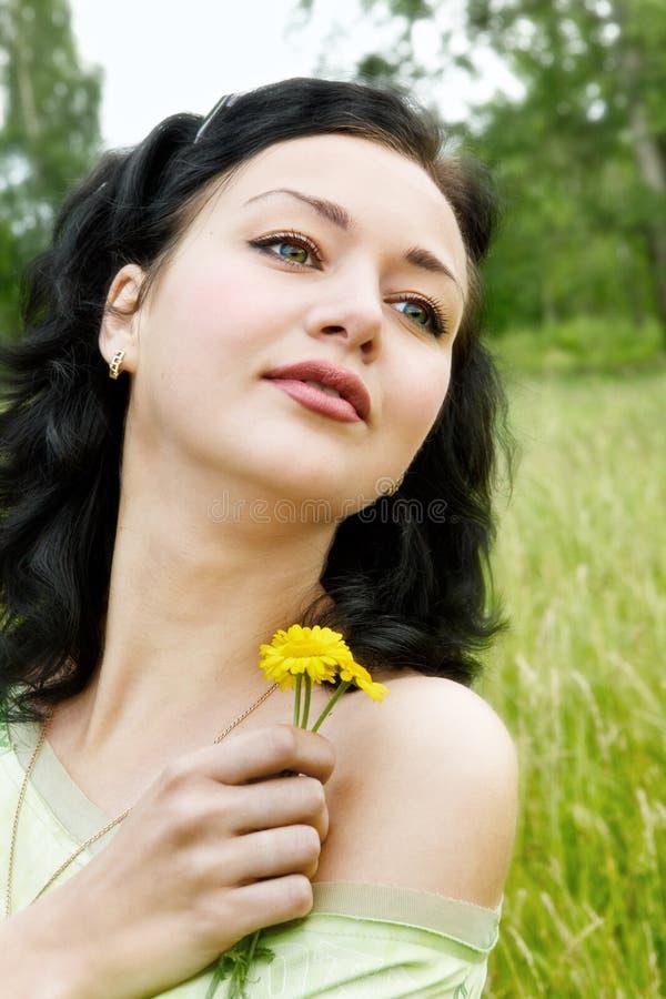 Giovane donna con i fiori selvaggi gialli fotografia stock libera da diritti