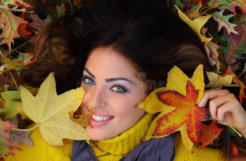 Giovane donna con i fogli di autunno fotografie stock libere da diritti