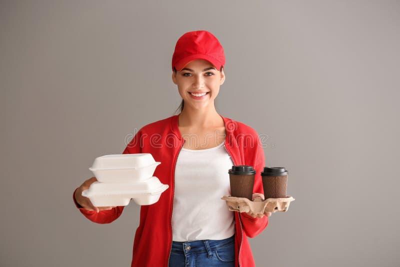 Giovane donna con i recipienti e le tazze di caffè di plastica su fondo grigio Servizio di distribuzione dell'alimento immagine stock