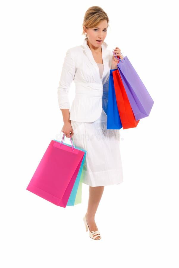 Giovane donna con i sacchetti di acquisto che si levano in piedi isolati immagini stock