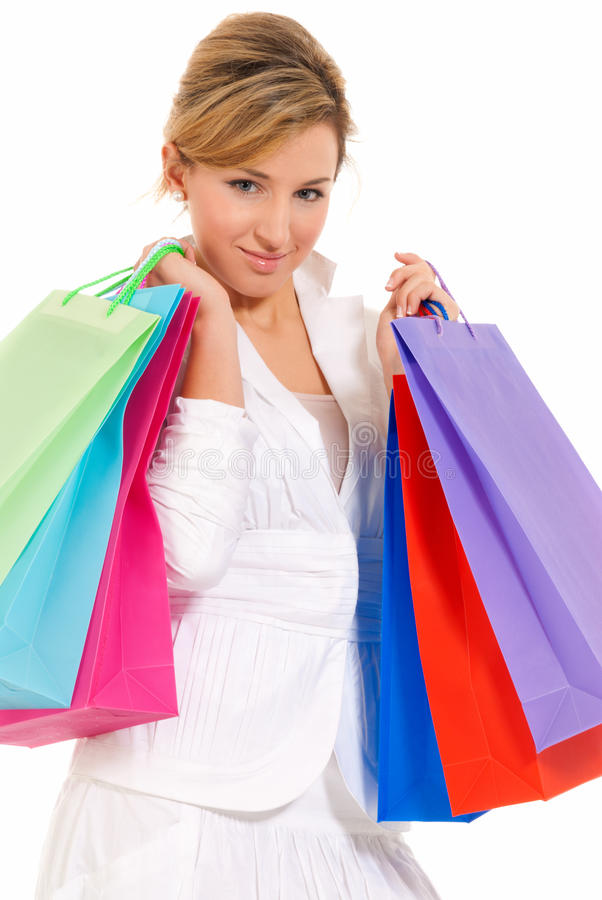 Giovane donna con i sacchetti di acquisto che si levano in piedi isolati fotografia stock