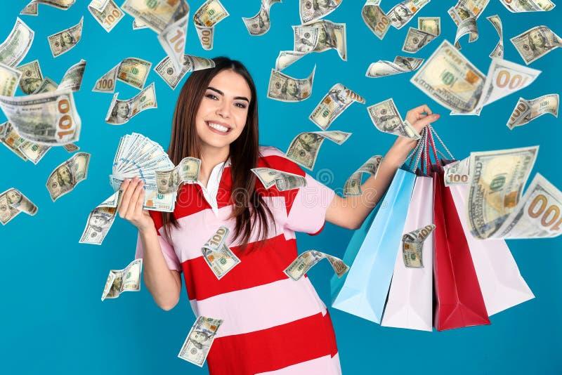 Giovane donna con i sacchetti di acquisto e dei soldi immagini stock libere da diritti
