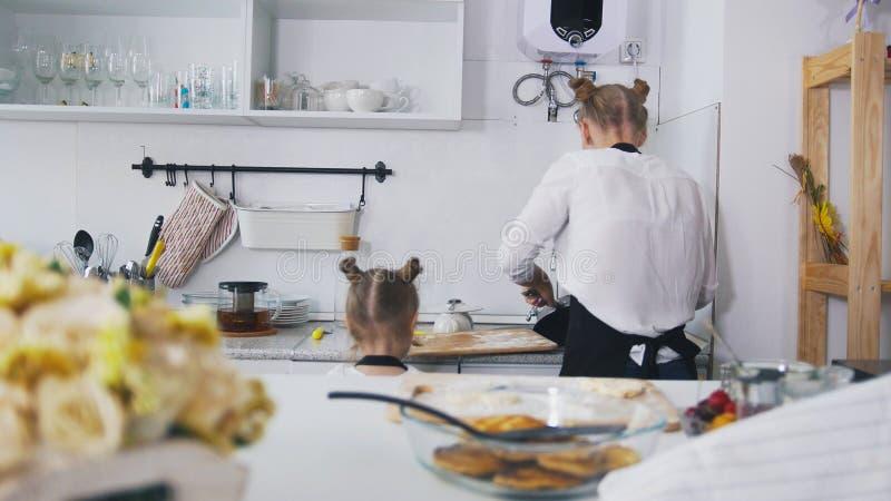 Giovane donna con i suoi piatti di lavaggio della figlia dopo la cottura immagine stock libera da diritti