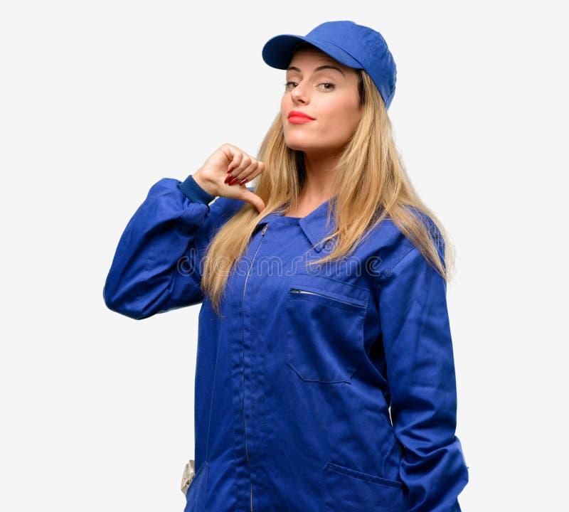 Giovane donna con i vestiti dell'idraulico isolati sopra fondo grigio immagini stock