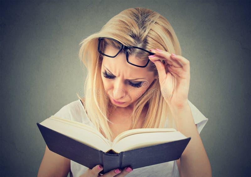 Giovane donna con i vetri che soffrono dall'affaticamento della vista dopo la lettura del libro fotografia stock libera da diritti