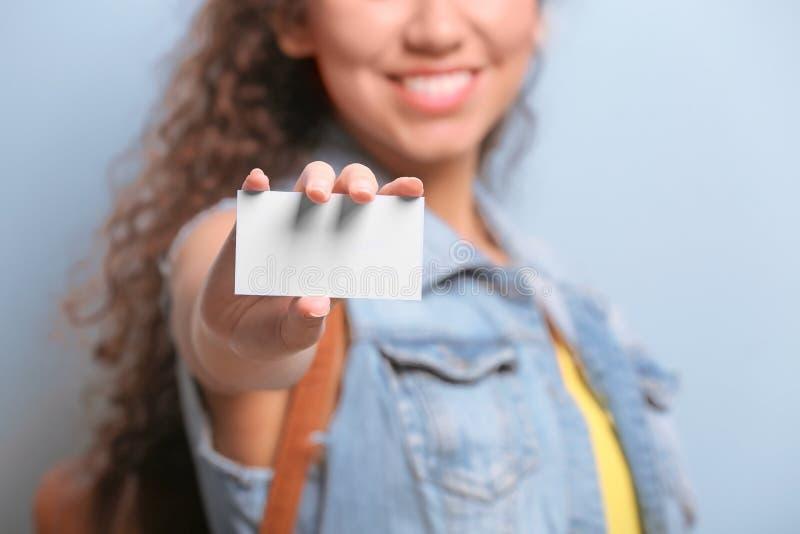 Giovane donna con il biglietto da visita sul fondo di colore immagini stock