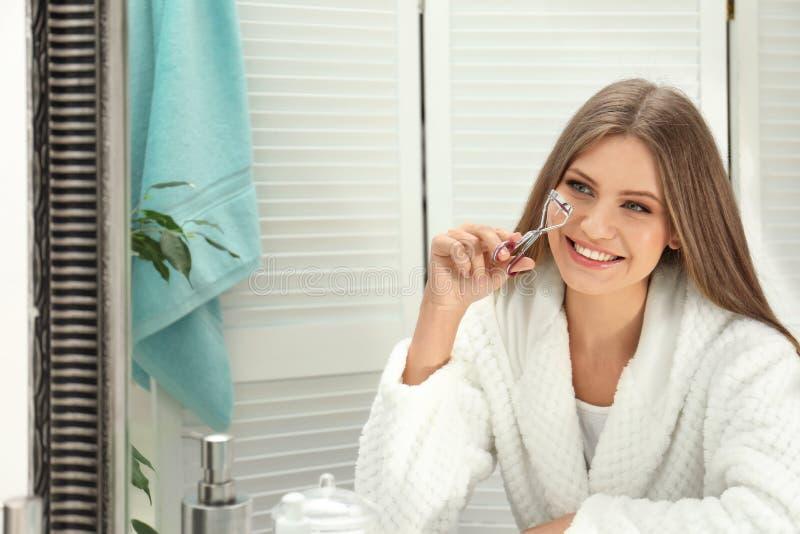 Giovane donna con il bigodino del ciglio vicino allo specchio fotografie stock