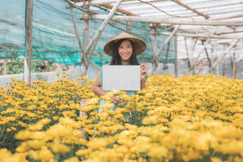 Giovane donna con il bordo bianco in bianco nell'azienda agricola del fiore fotografia stock libera da diritti