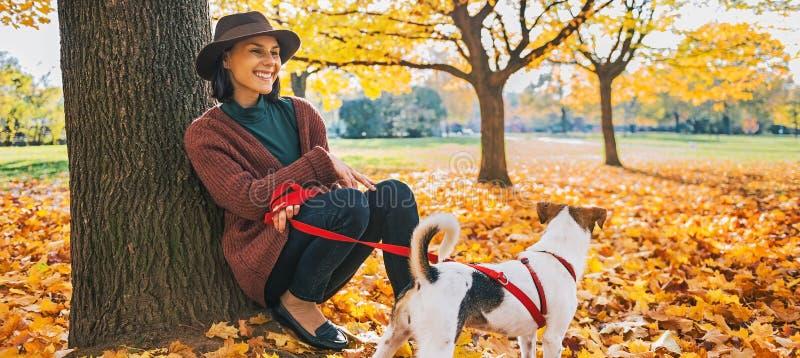 Giovane donna con il cane sveglio che si siede sotto l'albero nel parco di autunno fotografia stock libera da diritti