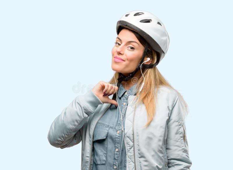 Giovane donna con il casco della bici e cuffie sopra fondo blu fotografia stock libera da diritti