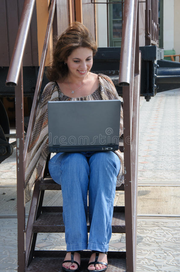 Giovane donna con il computer portatile sui punti di vecchio treno immagini stock