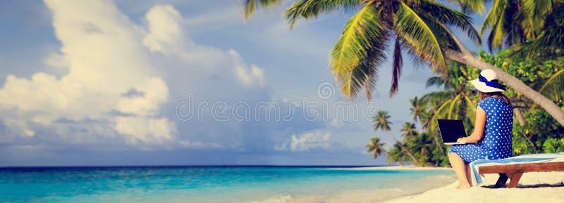 Giovane donna con il computer portatile sulla spiaggia tropicale immagine stock libera da diritti