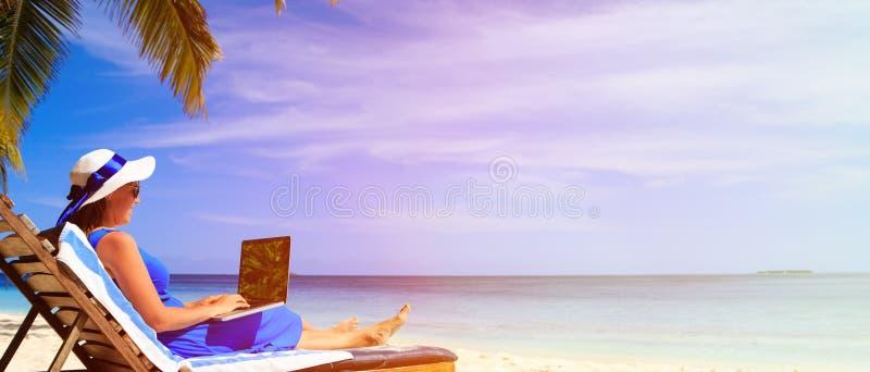 Giovane donna con il computer portatile sulla spiaggia tropicale fotografia stock