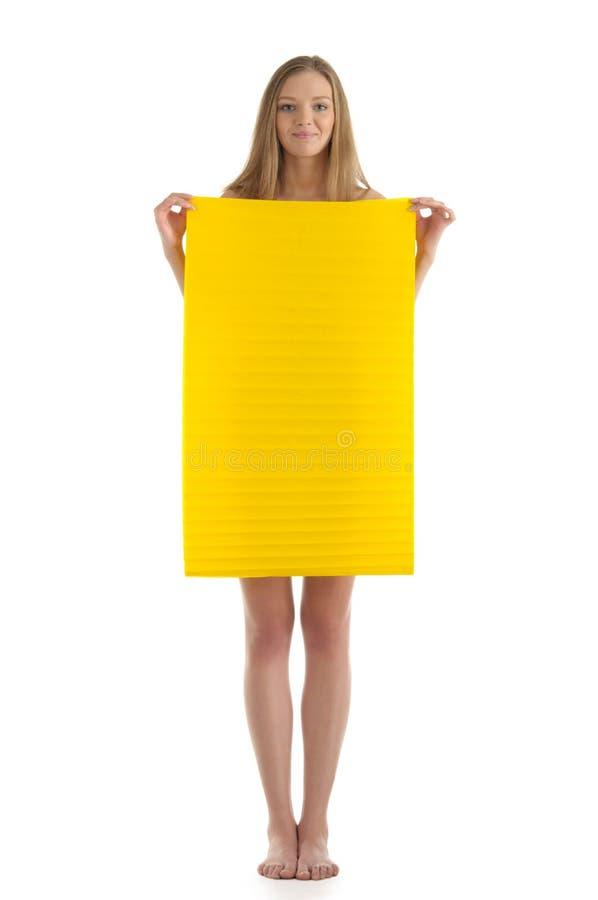 Giovane donna con il foglio di carta giallo fotografia stock