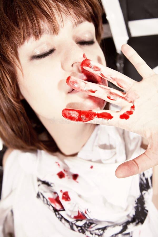 Giovane donna con il fronte macchiato di sangue fotografia stock